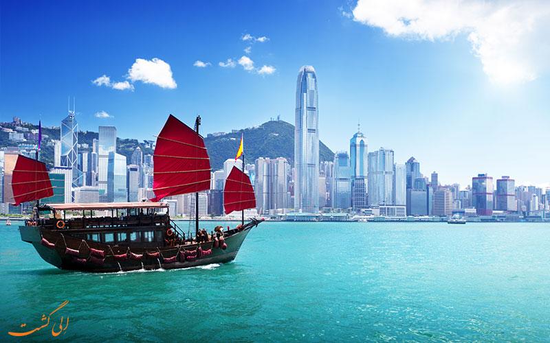 قایقی با بادبان قرمز رنگ روبروی بندر هنگ کنگ-تفاوت هنگکنگ، ماکائو و چین