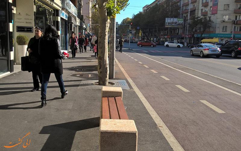 مردم در حال رفت و آمد در خیابان پکینی