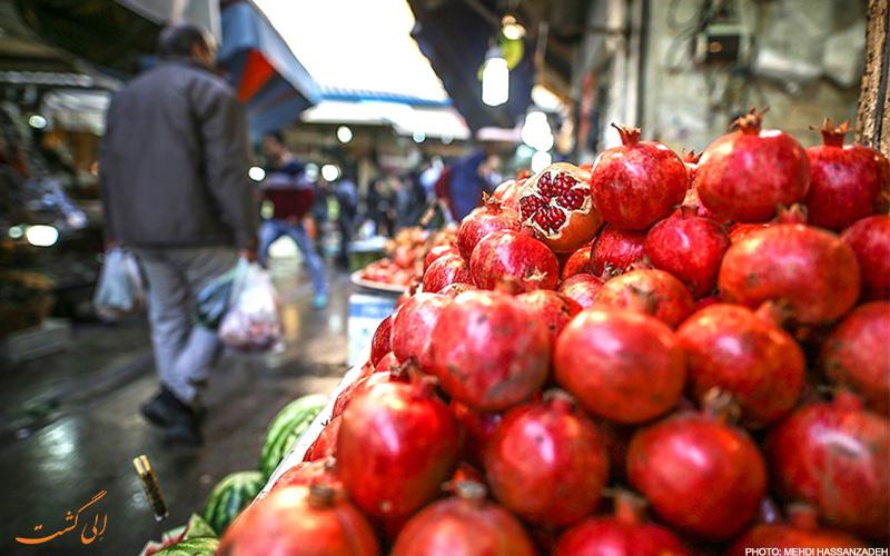 تصویر انار قرمز در بازار میوه فروشی با نمایی از خریدار در پشت